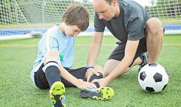 Niño que juega al fútbol con esguince de tobillo